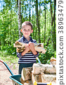 Little boy carries firewood from forest 38963479