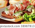 Bruschetta with ricotta, prosciutto, rucola on 38987813