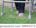 Elderly woman walking barefoot therapy on grass in backyard. 38993573