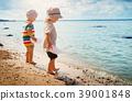 Babygirl and babyboy sitting on the beach 39001848