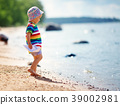 little boy playing at the beach in hat 39002981