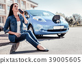 Young cute woman charging the car drinking cola. 39005605