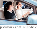 Satisfied pleasant friends sitting in the car and 39005617