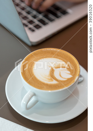 Hot art latte coffee cup on wooden table 39016320