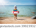 little boy playing at the beach in hat 39023932