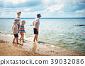 girl and boys standing on the beach in summer hats 39032086