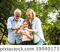 family holding a piggy bank and coins in a park 39040173