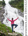 Female tourist observing beautiful waterfall in the mountains 39041022