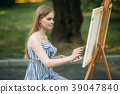 Beautiful girl draws a picture in the park using a 39047840