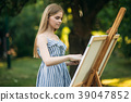 Beautiful girl draws a picture in the park using a 39047852