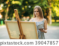 Beautiful girl draws a picture in the park using a 39047857