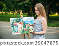 Beautiful girl draws a picture in the park using a 39047875
