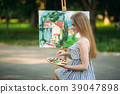 Beautiful girl draws a picture in the park using a 39047898