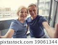 Laughing pensioners making selfie near window 39061344