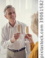 Celebrating pensioners holding sparkling wine 39061582