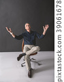 Appreciative old businessman sitting on chair 39061678