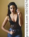 Beautiful brunette woman in black lingerie smoking cigarette 39070674