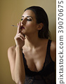 Young woman in black lingerie smoking cigarette 39070675