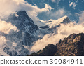 Mountains with snowy peaks in clouds at sunset 39084941