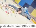 Climber on wall.Young man practicing rock climbing 39099104
