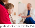Pediatrician write a prescription for boy 39107354