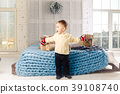 little funny playful boy a child sits on a bed on 39108740