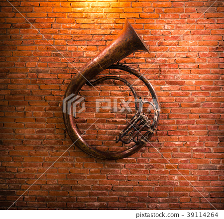 Old French horn on brick wall background. 39114264