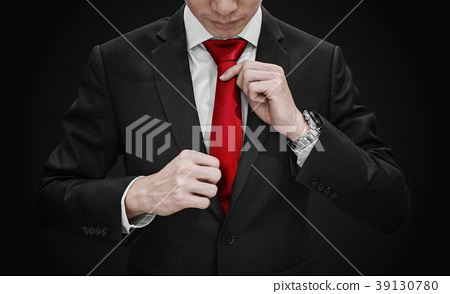 Businessman in black suit tying red necktie 39130780