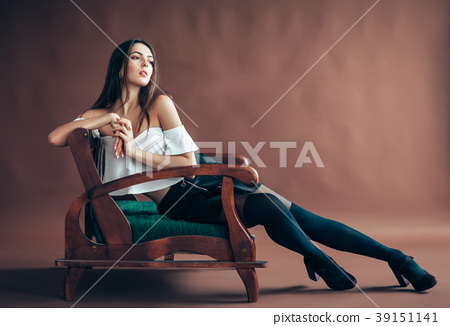 Beautiful woman posing on sofa on brown background 39151141