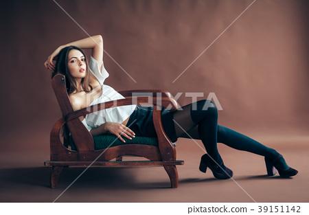 Beautiful woman posing on sofa on brown background 39151142