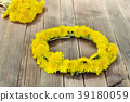 Wreath of dandelions on a wooden table. Summer 39180059