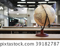 Globe placed on a wooden bookcase in the library 39182787