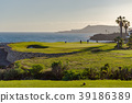 Golf players on a green facing the Atlantic  39186389
