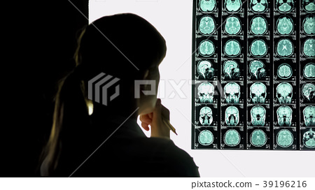 Thoughtful female doctor analyzing brain scan 39196216