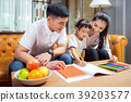 Asian father, mother and daughter doing home work  39203577