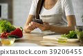 Woman choosing salad recipe on smartphone at the 39206455