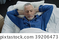 Top view of happy aged male lying in his bed and 39206473