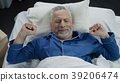 Pensioner stretching in his bed after awakening in 39206474