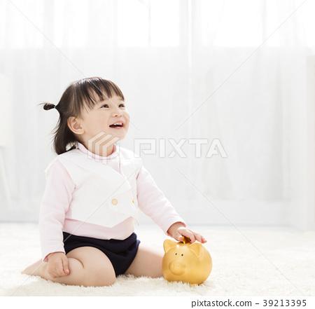 baby girl inserting a coin into piggybank 39213395