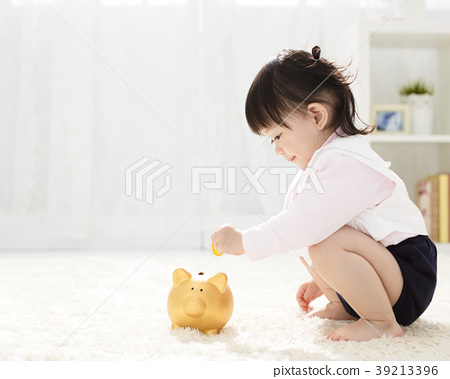 baby girl inserting a coin into piggybank 39213396