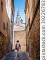 Woman walking by narrow street with tower of 39226783