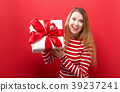 Happy young woman holding a gift box 39237241