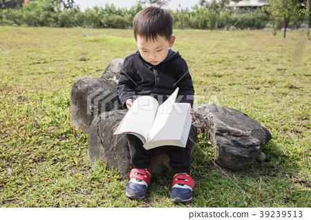學齡前兒童男孩在戶外場地坐在石頭上閱讀書本 39239513