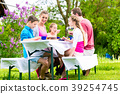 Family having coffee and cake in garden at house 39254745