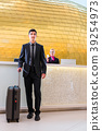 Man departing on business trip at hotel reception  39254973
