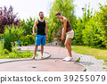 Couple playing together miniature golf outdoors 39255079