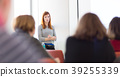 Woman giving presentation in lecture hall at 39255339