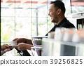Friendly bartender serving a short espresso to a 39256825