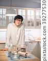 Young Asian man standing by counter in kitchen 39277530