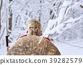 Brave spartan in winter forest looks in camera . 39282579